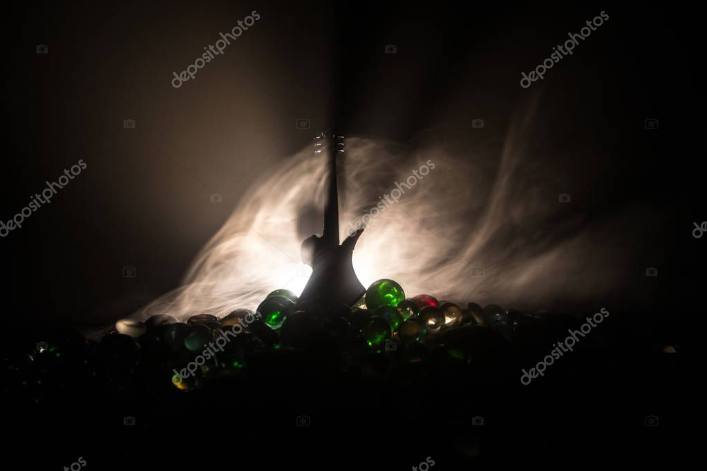 Music concept. Acoustic guitar on a dark background under beam of light with smoke. Emptry space for text. Fire effects. Surreal guitar