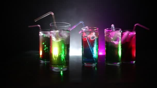 Fünf Cocktails an der Bar mit Rauch auf dunklem Hintergrund. gelbe, grüne und blaue Gläser.