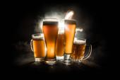 Tvůrčí koncept. Pivní brýle na dřevěném stolku na tmavém, mlhavé pozadí.