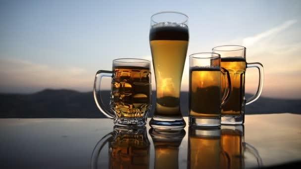 Sklenice piva na pláži při západu slunce. Ochlazování letního pití. Uzavření sklenice taženého piva s Bokehem slunečního světla, měkké zaostření