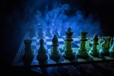 Chess board game concept of business ideas and competition. Chess figures on a dark background with smoke and fog. Selective focus stock vector
