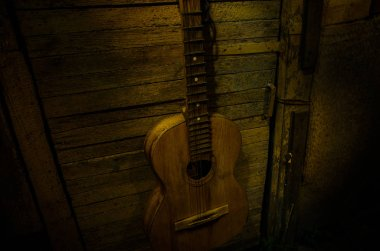 An wooden acoustic guitar is against a grunge textured wall. The room is dark with a spotlight for your copyspace.