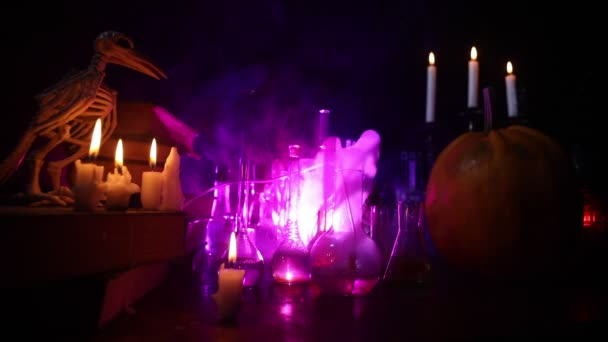 Varázslóasztal. Horror Halloween koncepció. Varázsital üvegben, fából készült asztalon, könyvekkel és gyertyákkal. Halloween csendélet háttér különböző elemek sötét tónusú ködös háttér.