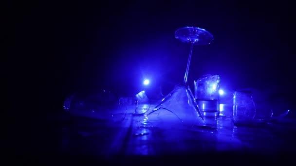 közeli felvétel törött üvegről az asztalon sötét alapon megvilágítással