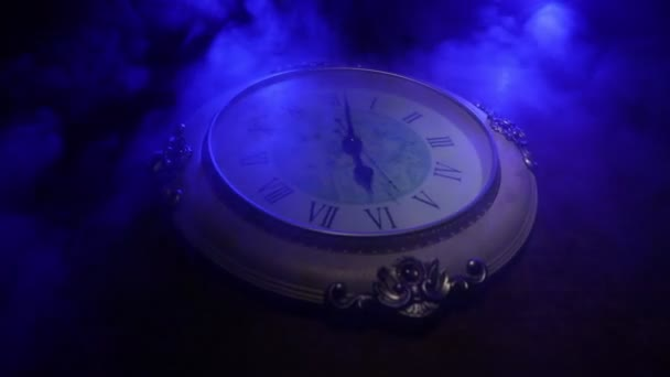 Időkoncepció. Nagy vintage kerek óra fa asztalon absztrakt fénnyel. Sötét légkör. Kreatív dekoráció. Szelektív fókusz