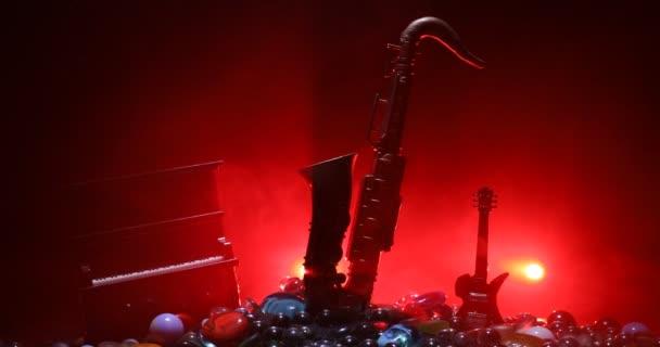 Zenei koncepció. Szaxofon jazz hangszer. Alto arany szaxofon miniatűr színes tónusú fény ködös háttér. Hangszerek alacsony fényben. Szelektív fókusz