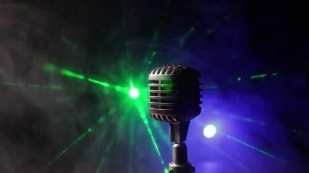 Mikrofon a sötét szobában az asztalon, hátsó fénnyel. Szelektív fókusz