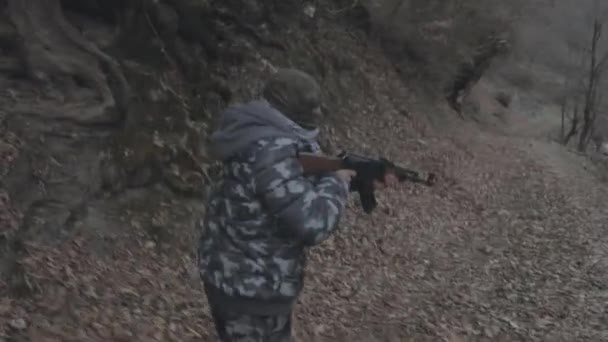 footage of man with assault riffle in forest