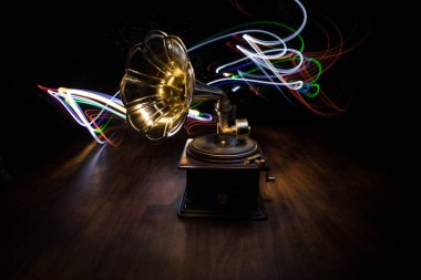 Music concept. Old gramophone on a dark background. Retro gramophone with disc on wooden table with toned backlight. Selective focus