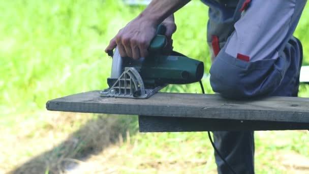 man sawing sawdust wood