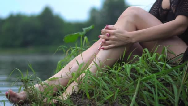 woman sitting on the grass by the river