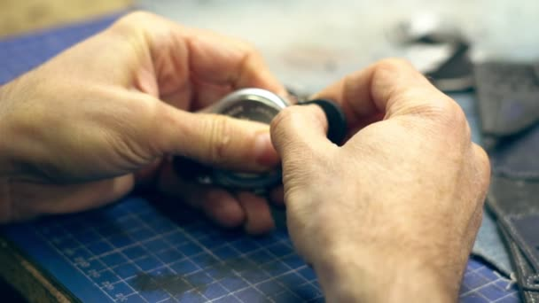 the watchmaker repairs the watch