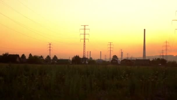 high-voltage towers at sunset near the houses