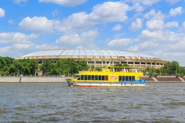 Moscow, Russia - May 30, 2018: Pleasure boat floating on a background of Big sports arena of the Olympic complex Luzhniki in sunny day
