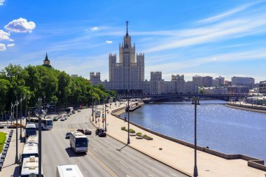 Moscow, Russia - June 03, 2018: Moskvoretskaya embankment of Moskva river against skyscraper on Kotelnicheskaya embankment on a sunny summer morning
