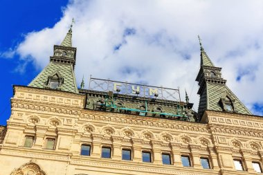 Moscow, Russia - September 30, 2018: Facade and towers on the roof of GUM Department store building on Red Square in Moscow against blue sky with white clouds
