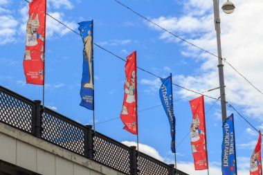 Moscow, Russia - June 21, 2018: Red and blue flags with symbols of FIFA World Cup Russia 2018 closeup on the railing of the bridge against blue sky at summer day