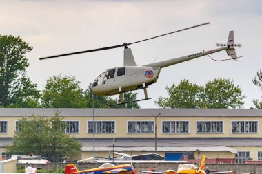 Balashikha, Moscow region, Russia - May 25, 2019: Helicopter Robinson R44 Raven RA-06359 flies against building and green trees over airfield Chyornoe at the Aviation festival Sky Theory and Practice