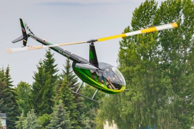Balashikha, Moscow region, Russia - May 25, 2019: Helicopter Robinson R44 Raven RA-07368 flies against green trees over airfield Chyornoe at the Aviation festival Sky Theory and Practice 2019