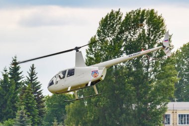 Balashikha, Moscow region, Russia - May 25, 2019: Helicopter Robinson R44 Raven RA-06359 flies against green trees over airfield Chyornoe at the Aviation festival Sky Theory and Practice 2019