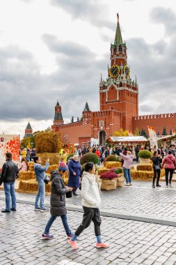 Moscow, Russia - October 05, 2019: Exposition of traditional festival Golden Autumn on Red Square against Spasskaya tower of Moscow Kremlin in cloudy autumn day