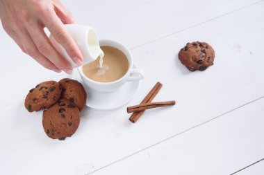 A woman's hand pours milk into coffee. A cup of fragrant coffee with cinnamon and cookies on a white background.