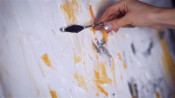 Close up artists hand with mastic and yellow paint slides on white canvas.