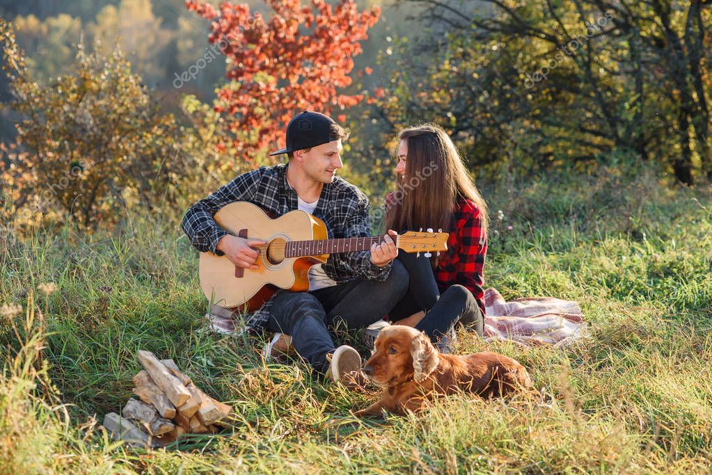 Happy caucasian couple with guitar and their dog having rest on picnic in the park on the lawn.