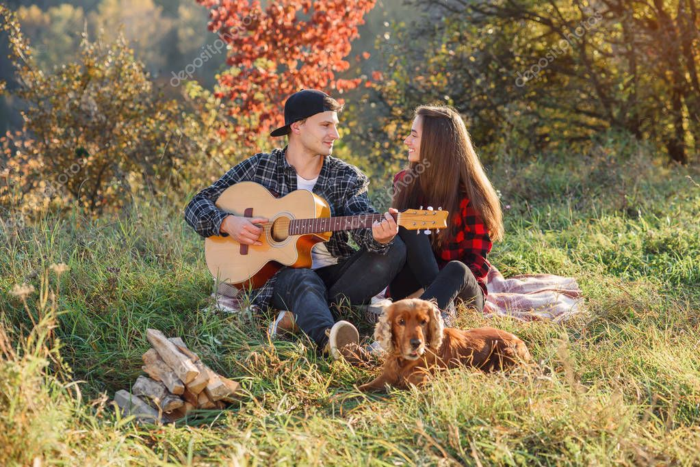 Happy lovely couple in casual clothes with guitar and their dog having rest on picnic in the park.