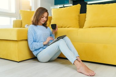 Charming girl holds her tablet computer in hands, sitting on the floor near modern yellow couch and drinks coffee in the modern stylish kitchen. Young cheerful woman having rest at cozy home.