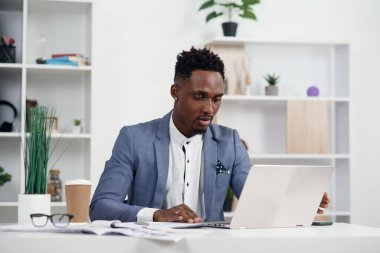 Serious dark-skinned young office manager works with different reports and table laptop at his workplace in the meeting room at modern business centre.