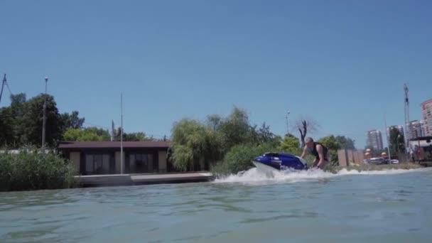 mladý muž je jízda hydrocycle na jezeře