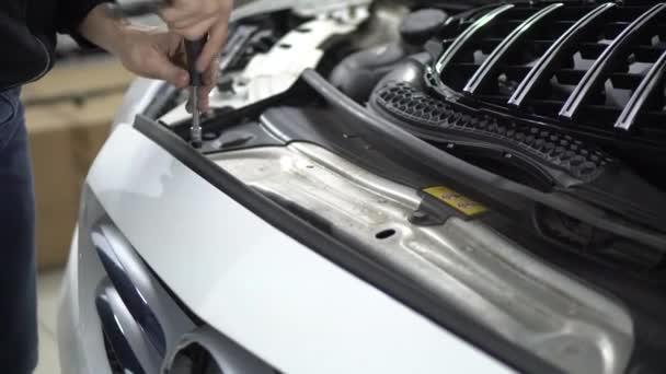szerelő unscrews biztosítása a lökhárító autó bolt