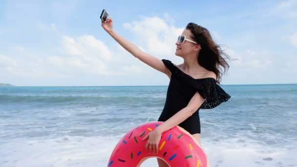 Sexy mladá žena s kobliha float a sluneční brýle, mají zábavu a těší letní prázdniny na tropické pláži dovolenou. Relax žena v swimdress, takže selfie na pláži. Roztomilá dívka s hračkami se těší