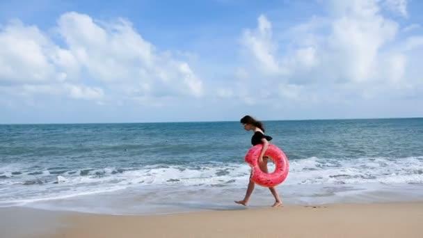 Atraktivní mladá žena s plovoucí Kobliha, mají zábavu a těší letní prázdniny na tropické pláži dovolenou. Relax žena v swimdress baví na pláži. Krásná dívka s hračkami se těší