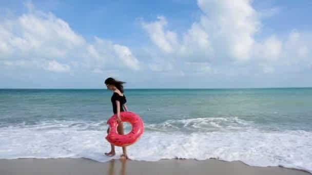 Šťastná mladá žena s plovoucí Kobliha, chůzi na tropické pláži dovolenou. Relax žena v plavky baví na pláži. Krásná dívka s hračkami dovolenou se těší a baví na břehu moře