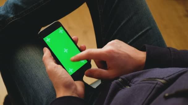 Guy v neformálním oblečení drží smartphone s zeleným plátnem