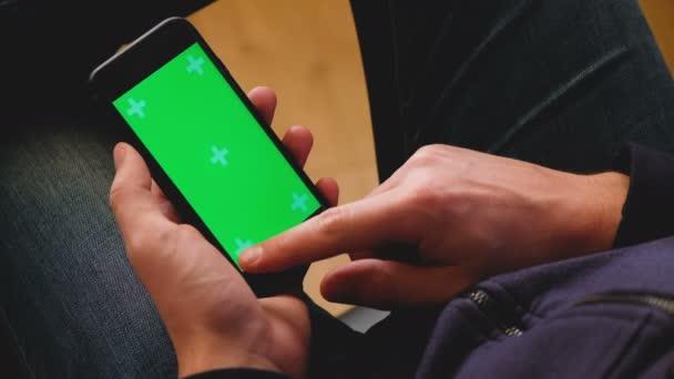Ember, leafing keresztül egy smartphone-val egy zöld képernyő fotók