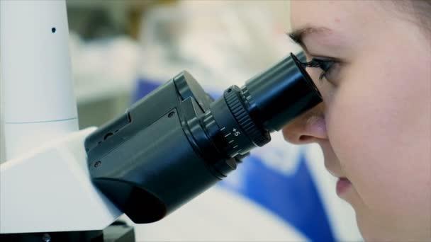 Scientist looking through a microscope and examining a new dangerous virus