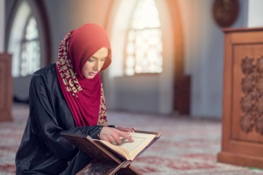 Muslim Woman Reading Koran Or Quran Wearing Traditional Dress At The Mosque