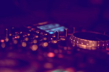 Dj mixes the track in the nightclub at party. DJ hands in motion