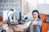 Schöne Geschäftsleute mit Kopfhörern benutzen Computer und lächeln im Büro. Mädchen blickt in Kamera