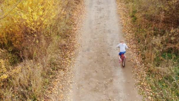 Mädchen fährt Fahrrad auf Landstraße