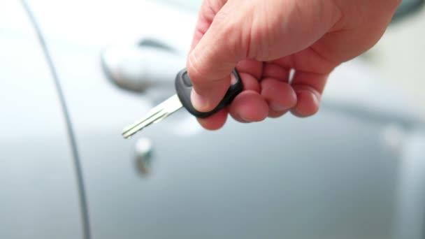 Mužova ruka otevírá dveře auta s klíčem