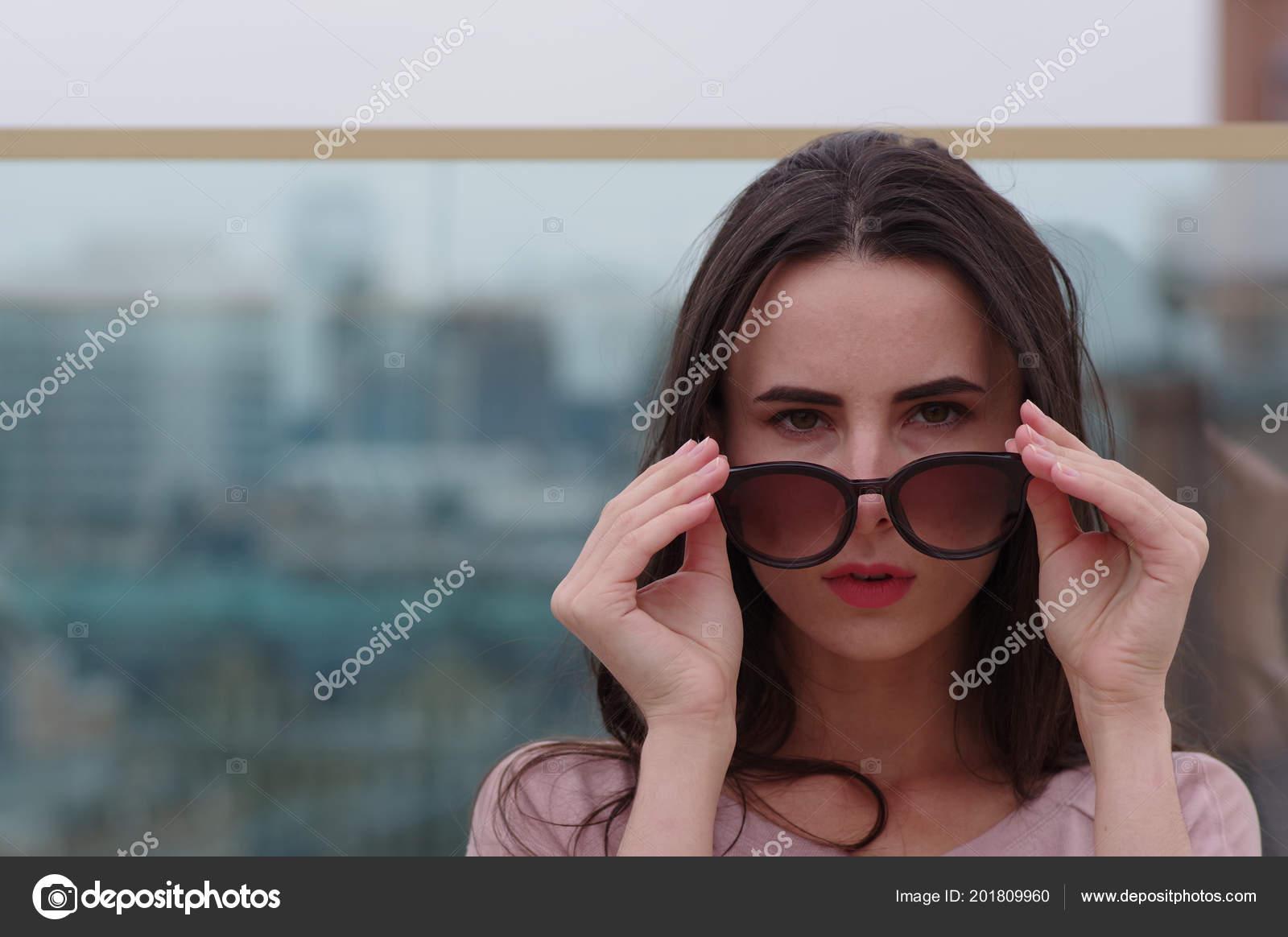 b5949960f8 Ένας μακρυμάλλης μελαχρινή νεαρή γυναίκα παίζει με τα γυαλιά ηλίου– εικόνα  αρχείου