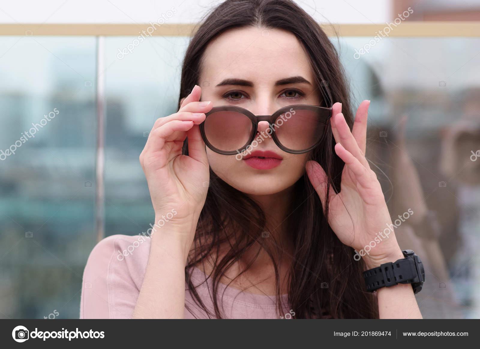e943961012 Γκρο πλαν  μακρυμάλλης νεαρή γυναίκα μελαχρινή ποζάρουν παίζοντας με γυαλιά  ηλίου. Μοντέρνο στυλ με ροζ τόνους. Θολή φόντο. Ο αγέρας παίζει με τα  μαλλιά ...