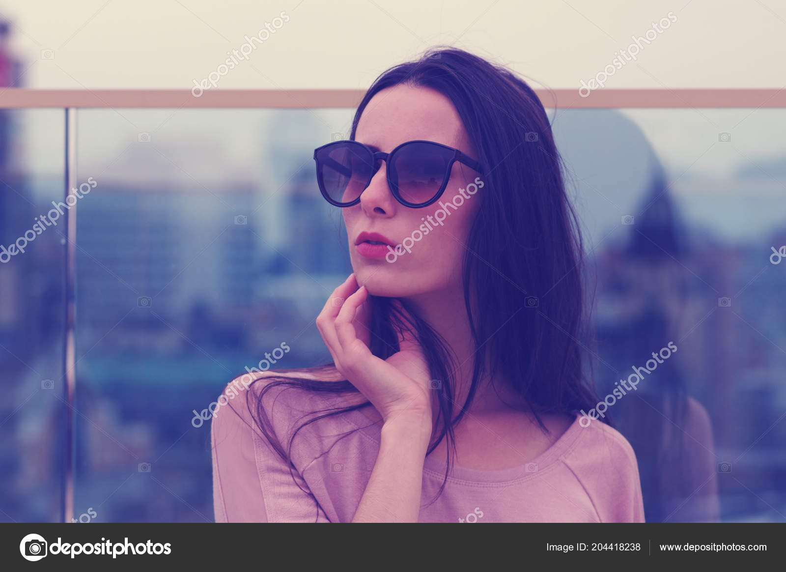b5efebb659 Μακρυμάλλης νεαρή γυναίκα μελαχρινή ποζάρουν σε μεγάλα γυαλιά ηλίου.  Μοντέρνο στυλ με ροζ τόνους.