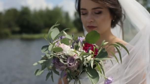 Portrét nevěsty ve svatebních šatech s květy kytice