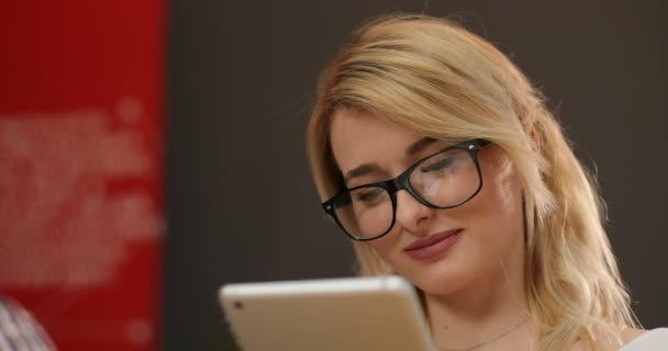 Portrait of gorgeous young businesslady in glasses at her workplace using tablet computer