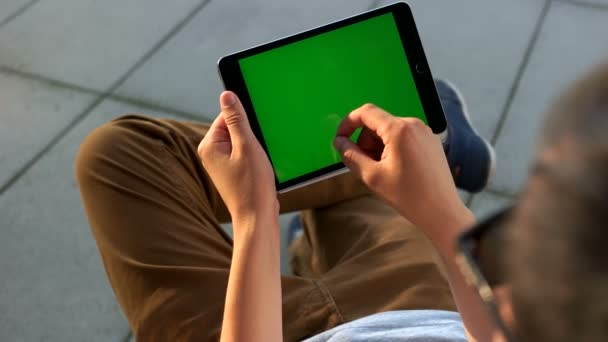 Man hands using tablet with green screen for chatting with friends at the airport. Close up. Chroma key.